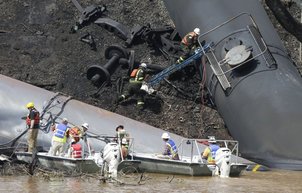 Workers remove damaged cars Thursday along the tracks where several CSX tanker cars carrying crude oil derailed and caught fire along the James River near downtown Lynchburg, Va. Two cranes were lifting derailed cars and moving them to a new track.