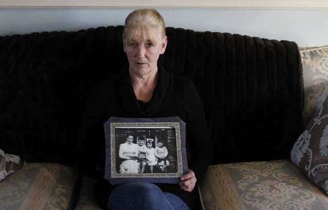 Helen McKendry, at home in Killyleagh, Northern Ireland, holds an old family photo that shows her mother, Jean McConville. Sinn Fein leader Gerry Adams has been arrested in connection with McConville's slaying in 1972.