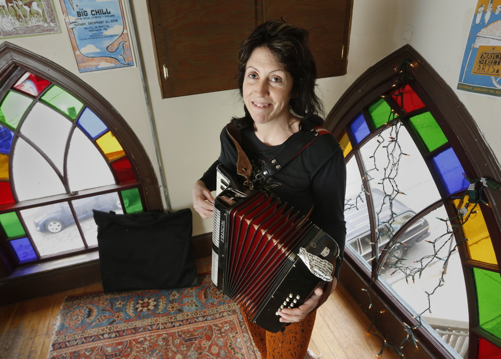 """Blainor McGough, 39, a puppeteer and musician who manages the Mayo Street Arts performance venue in Portland, plays the accordion at her home Thursday. A native Mainer who lived and worked in, among other places, Florida and Mexico, she eventually returned. """"I realized there was no place else I'd want to live,"""" she said."""