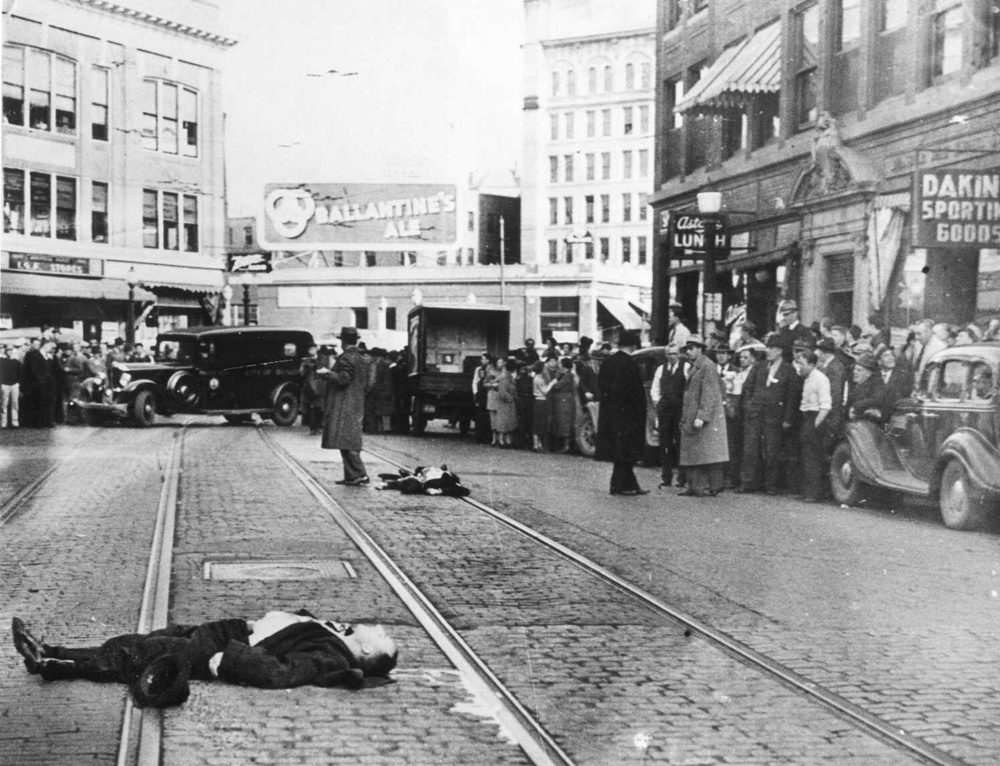 Gangsters Al Brady, foreground, and Clarence Lee Shaffer Jr., background center, lie on Central Street were they were killed by government agents Oct. 12, 1937, in Bangor. FBI agent Walter R. Walsh, who posed as a salesman, was wounded in the incident.