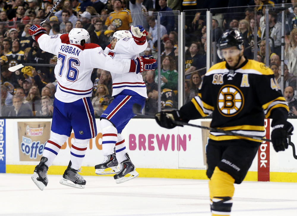Montreal Canadiens defenseman Francis Bouillon jumps with defenseman P.K. Subban (76) to celebrate his goal as Boston Bruins center David Krejci, right, skates away during the third period Thursday.