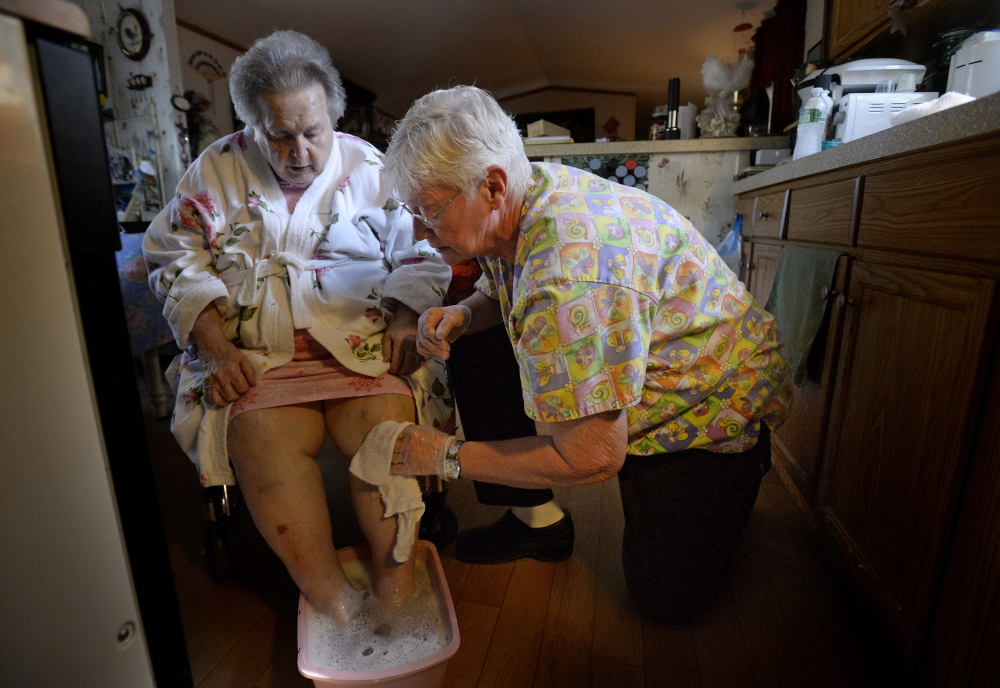 Mildred Rood, 85, at left, is able to stay in her Windsor home thanks in part to the personal care services she receives from Nancy Boily, seen here washing her client's feet and legs with warm water in order to ease their pain and numbness. Compensation for Maine's home care workers hasn't kept up with the increasing demand for their services.