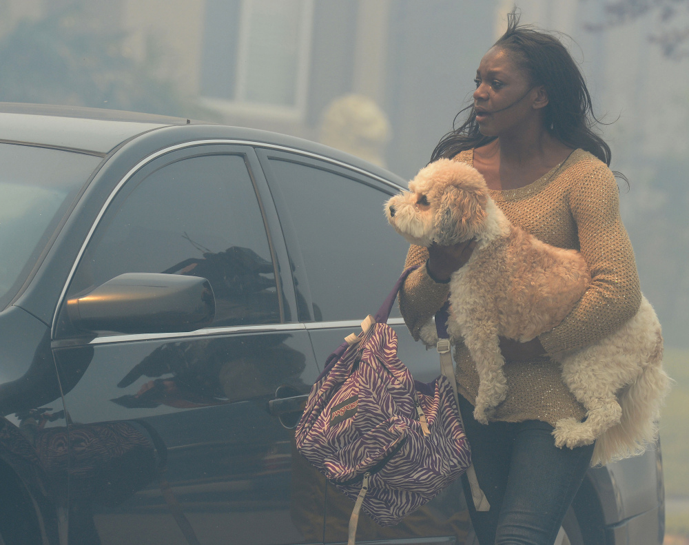 A woman evacuating her home carries a dog to a vehicle in smoke from the Etiwanda Fire in Rancho Cucamonga, Calif., on Wednesday. The wildfire driven by surging Santa Ana winds sent a choking pall of smoke through foothill neighborhoods. No homes burned, but the smoke prompted mandatory evacuation orders for several areas of town.
