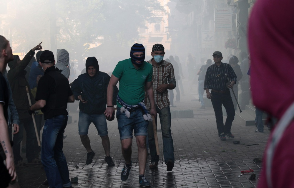 A Ukrainian government supporter holds a stone and a stick during a clash with pro-Russians in Odessa, Ukraine, Friday.