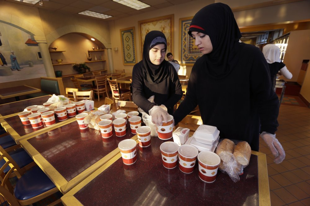 Volunteers Wafaa Dabaja, left, and Zahraa Dabaja prepare meals from food provided by the Yasmeen Bakery in Dearborn, Mich.