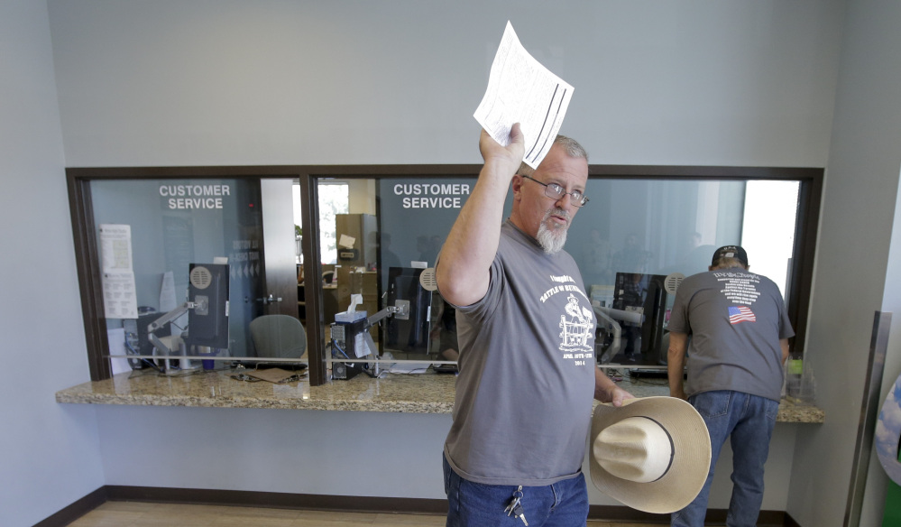 Sean Harron, a supporter of Cliven Bundy, waves after turning in a complaint against the Bureau of Land Management at the Metropolitan Police Department in Las Vegas on Friday.