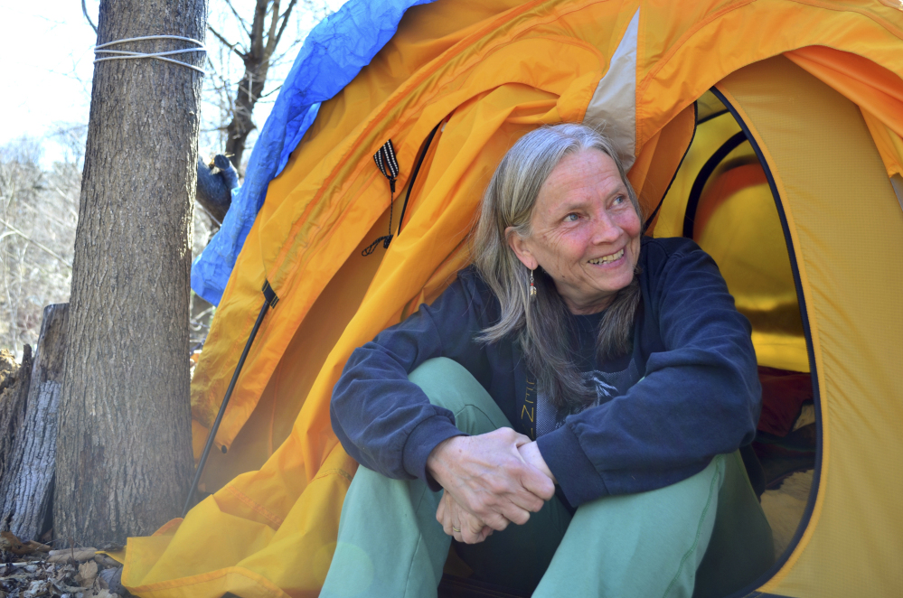 Nina Miller sits in the opening of her tent in the woods behind her home, where she has slept for more than 170 nights.
