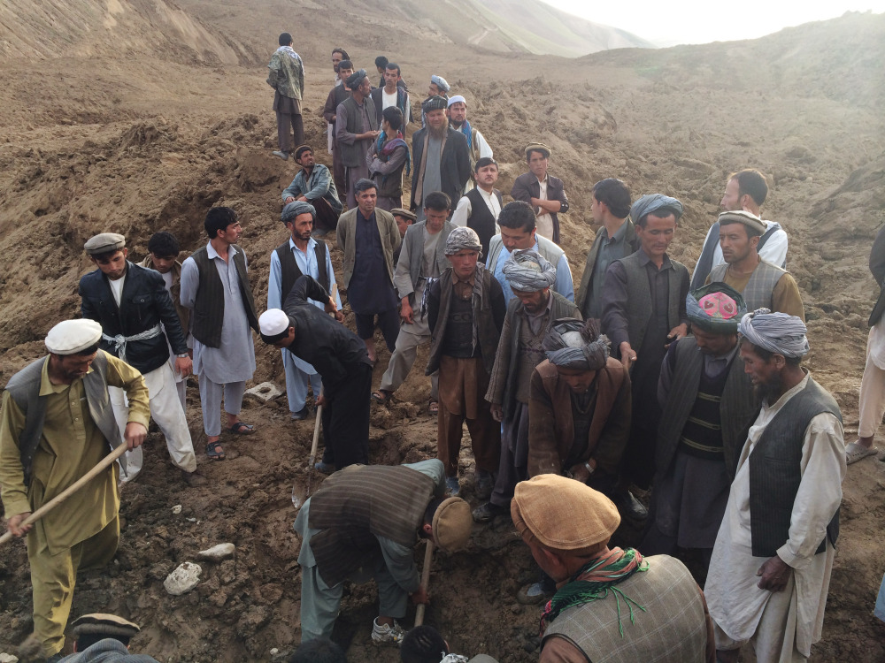 In this Friday, May 2, 2014 photo provided by Homayoon Rahmani, chief of road reconstruction program in the Afghan Rural and Rehabilitation Development Ministry, Afghans search for survivors buried after a massive landslide in a village in Badakshan province, northeastern Afghanistan.