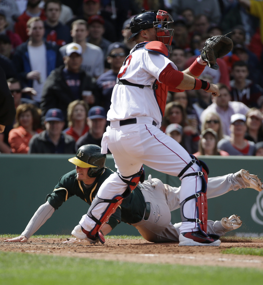 Oakland's Josh Donaldson slides home ahead of the tag by Red Sox catcher A.J. Pierzynski to score on a sixth-inning double by Yoenis Cespedes, who later drove home the winning run in the 10th inning with a bases-loaded infield single.