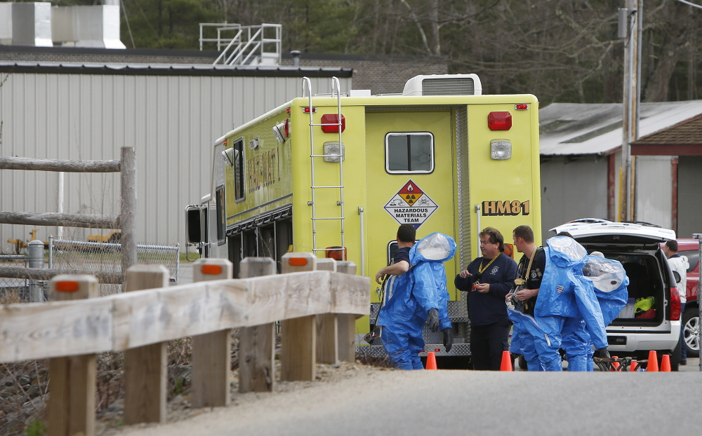 Hazardous materials team members from the Portsmouth Naval Shipyard remove hazmat suits after responding to an explosion at the sewage treatment plant in Kennebunk on Monday.