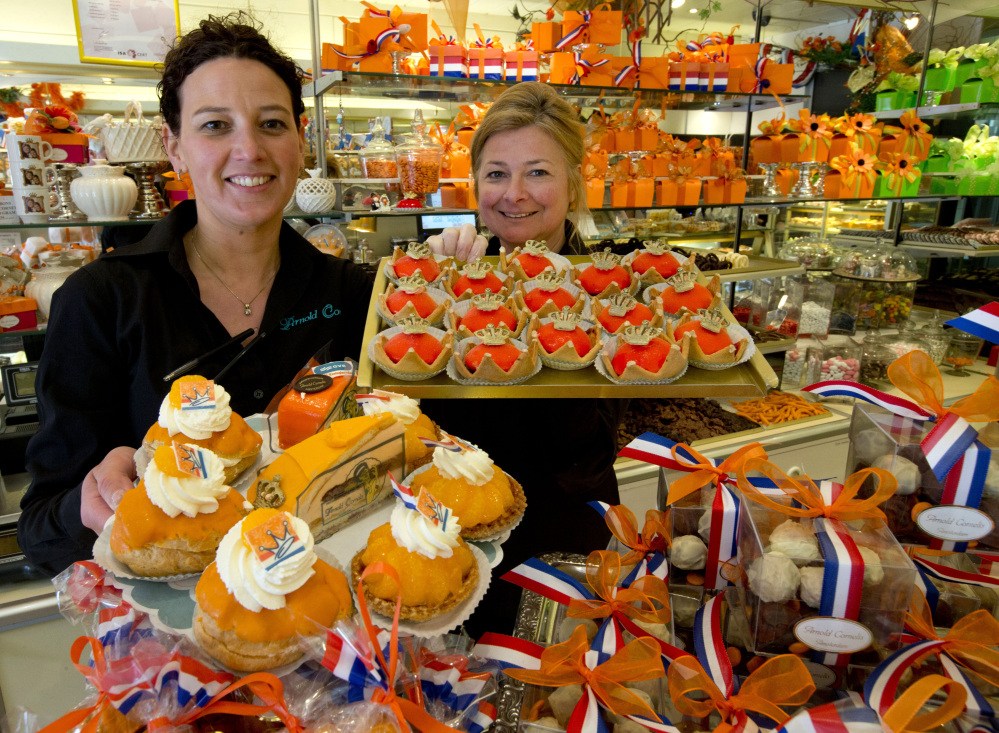 Sandra Terpstra, left, and Linda Clewits hold trays of cakes at an Arnold Cornelis pastry shop in Amsterdam. The restaurant chain Dunkin' Donuts is expanding in Europe.