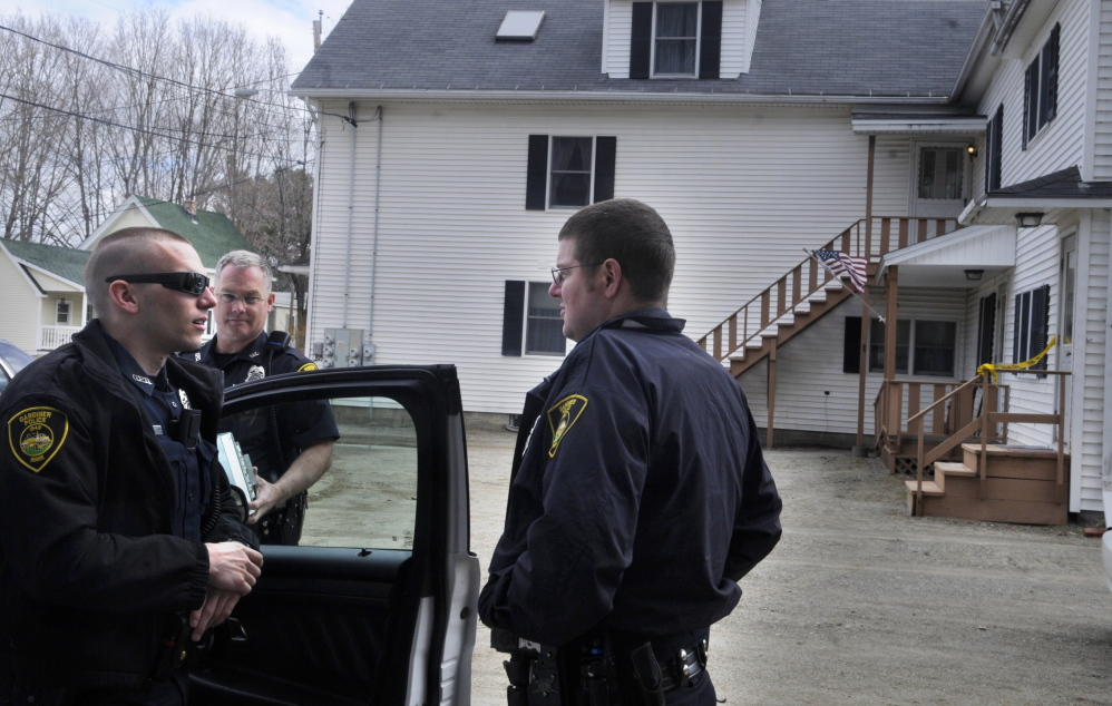 Gardiner police confer Monday while guarding an apartment building on Cannard Street where a father and son lived together. Maine State Police searched their apartment.