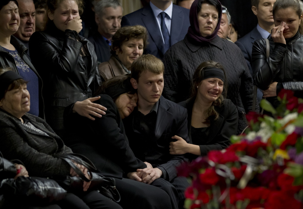 "Mourners cry next the coffin of regional parliament member Vyacheslav Markin in Odessa, Ukraine, on Monday. Markin, who was known for speaking out against the government in Kiev, was buried Monday while about 300 pro-Russian supporters shouted ""Hero, hero!"" Markin died Sunday from burns sustained in Friday's fire."