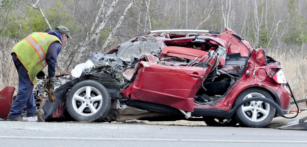 The crumpled wreckage of a small car is examined after a collision with a Vassalboro school bus that was parked on Route 3 in South China on Monday.