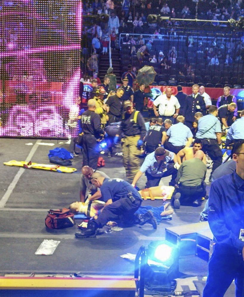 In this photo provided by Rose Viveiros, first responders work at the center ring after a platform collapsed during an aerial hair-hanging stunt at the Ringling Brothers and Barnum and Bailey Circus, Sunday in Providence, R.I. At least nine performers were seriously injured in the fall, including a dancer below, while an unknown number of others suffered minor injuries.