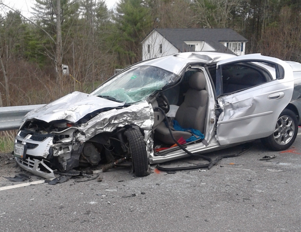 A woman is in satisfactory condition after a head-on crash in Newfield totaled this car. Police said a pickup driver bent over to pick up his cellphone just before the accident.