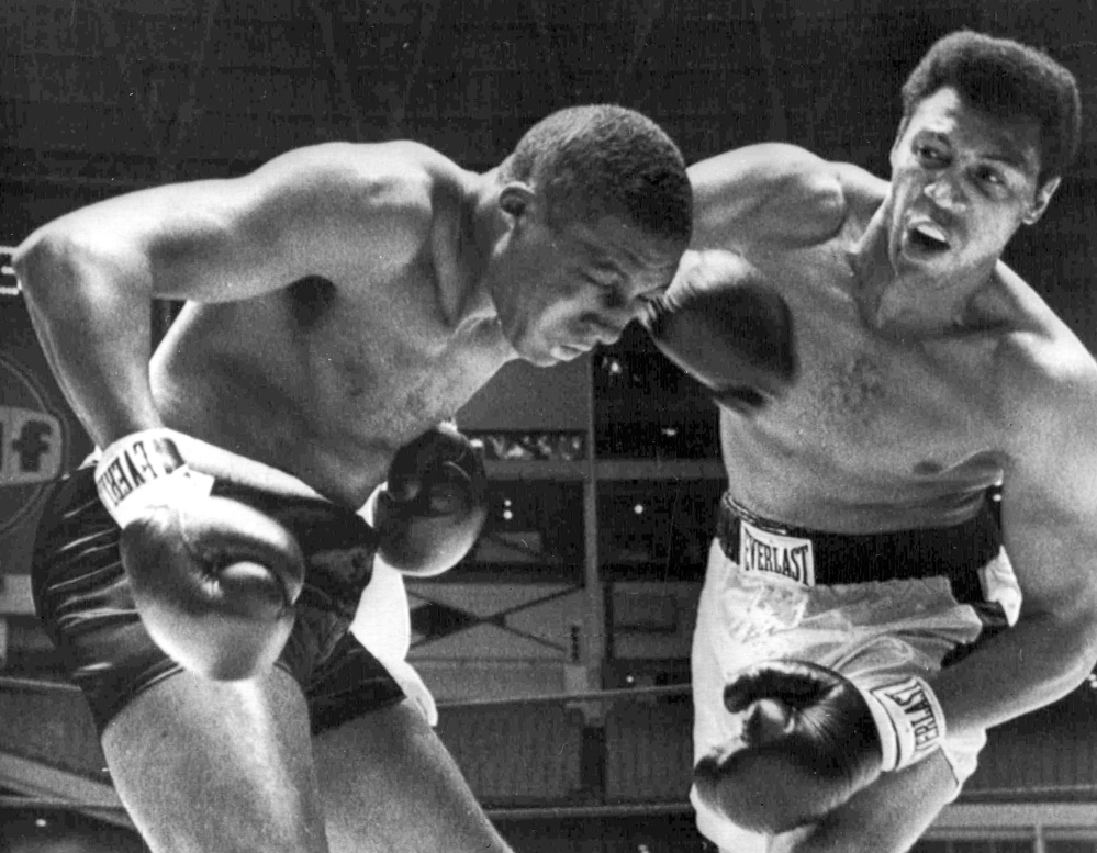 Jimmy Ellis, right, delivers a right hook to the head of Leotis Martin during their 12-round World Heavyweight title elimination fight in Houston, Texas. Ellis, who won the 1968 championship, died Tuesday. He had suffered from dementia for more than a decade.