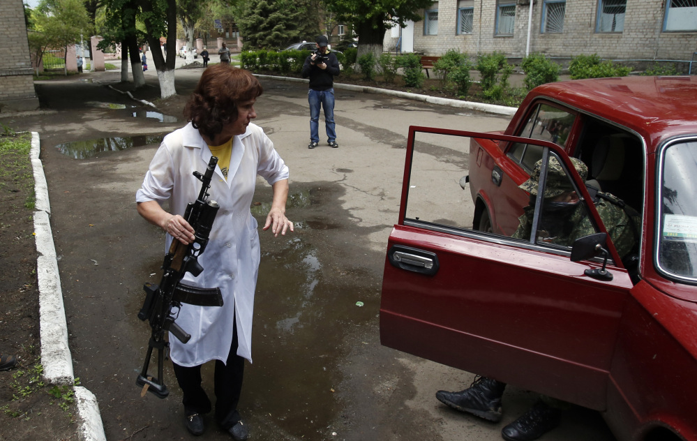 A nurse holds a gun as she helps a wounded pro-Russian gunman out of a car in front of a hospital in Slovyansk, eastern Ukraine, on Monday.