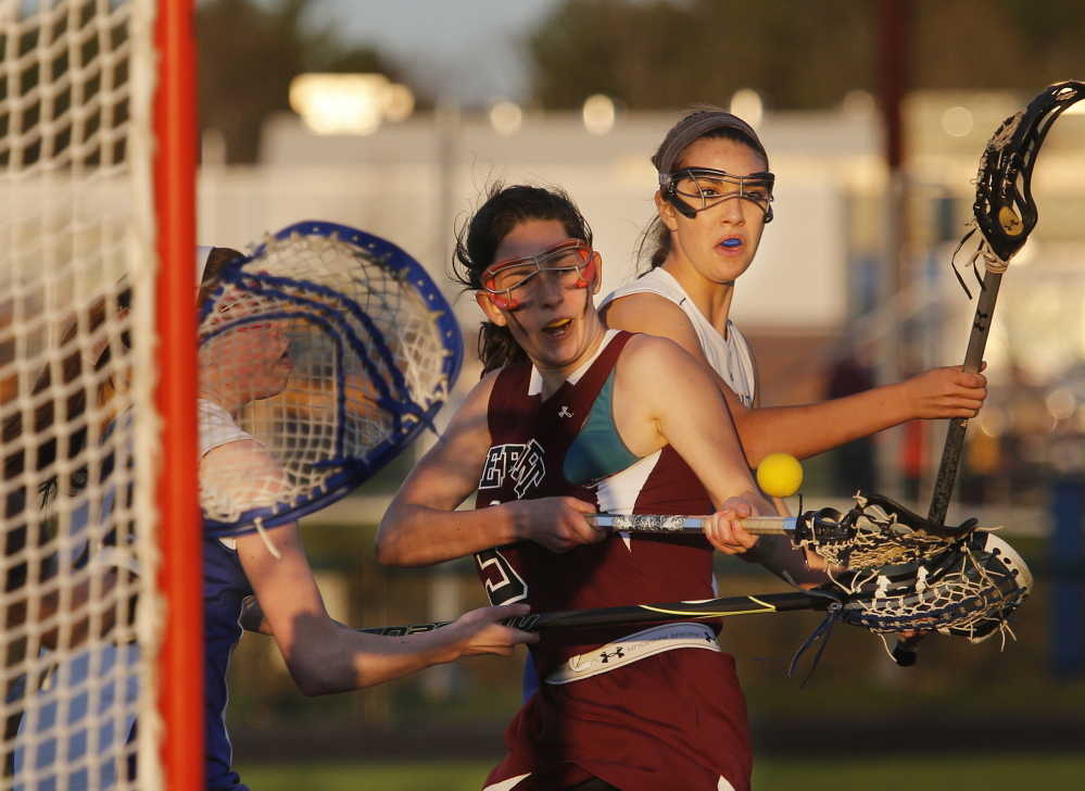 Olivia Stucker of Falmouth, left, denies a shot attempt by Lizzie Martin of Freeport during their girls' lacrosse game Wednesday. Martin scored two goals as the Falcons came away with an 8-7 victory.