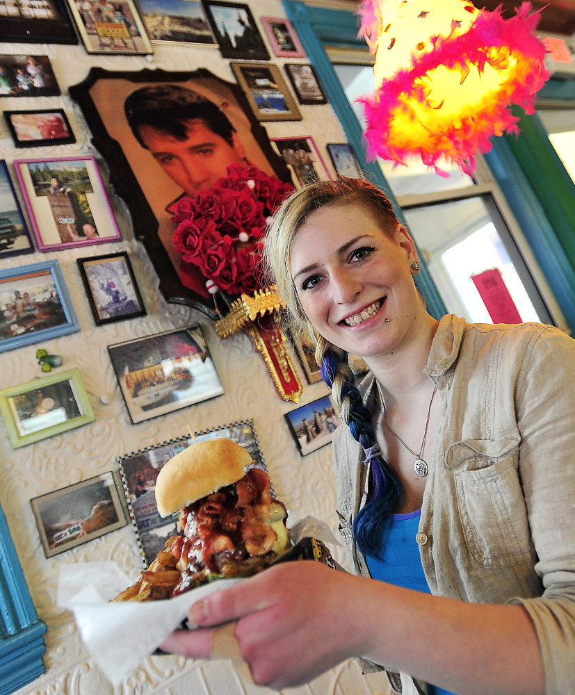 Surrounded by Silly's signature quirky art, hostess Callie Steinberg shows off a specialty cheeseburger called Bleu Swayed 'Cue, made with two charbroiled hand-formed beef patties, pickles, cheddar, barbecue sauce, bacon, caramelized onions and blue cheese crumbles, with fries.