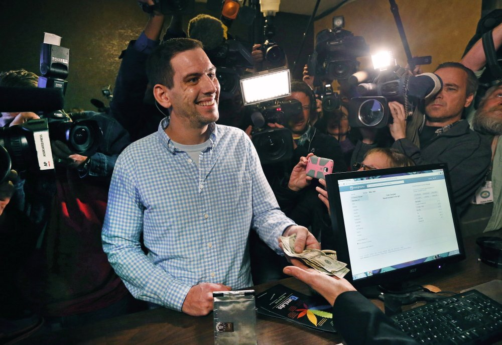 Sean Azzariti makes a cash transaction on Jan. 1 when a retail marijuana outlet opened for the first time in Denver. Lawmakers there now are crafting a way for such businesses to handle their money, which banks have declined to do.