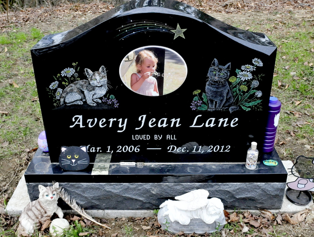Avery Lane's grave at the Friends Cemetery has a polished black granite marker that's etched with a photo of her blowing bubbles, along with engraved images of two cats.