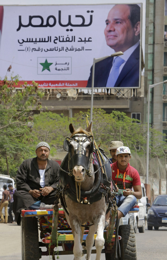 Egyptian villagers make their way on a horse cart past a campaign billboard of presidential hopeful Abdel-Fattah el-Sissi in Cairo, Egypt, on Thursday.