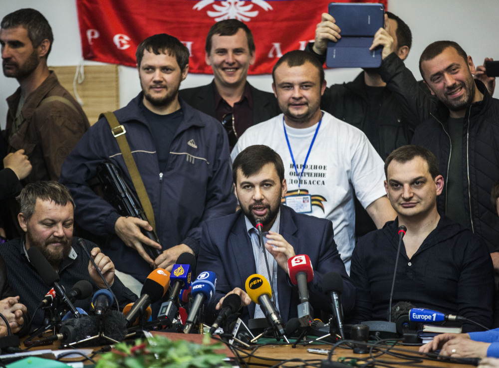 Denis Pushilin, center foreground, who heads the elections commission of the pro-Russian group that calls itself Donetsk People's Republic, speaks Thursday about the upcoming referendum to be held in eastern Ukraine. The news conference was held in the occupied administration building in Donetsk, Ukraine.