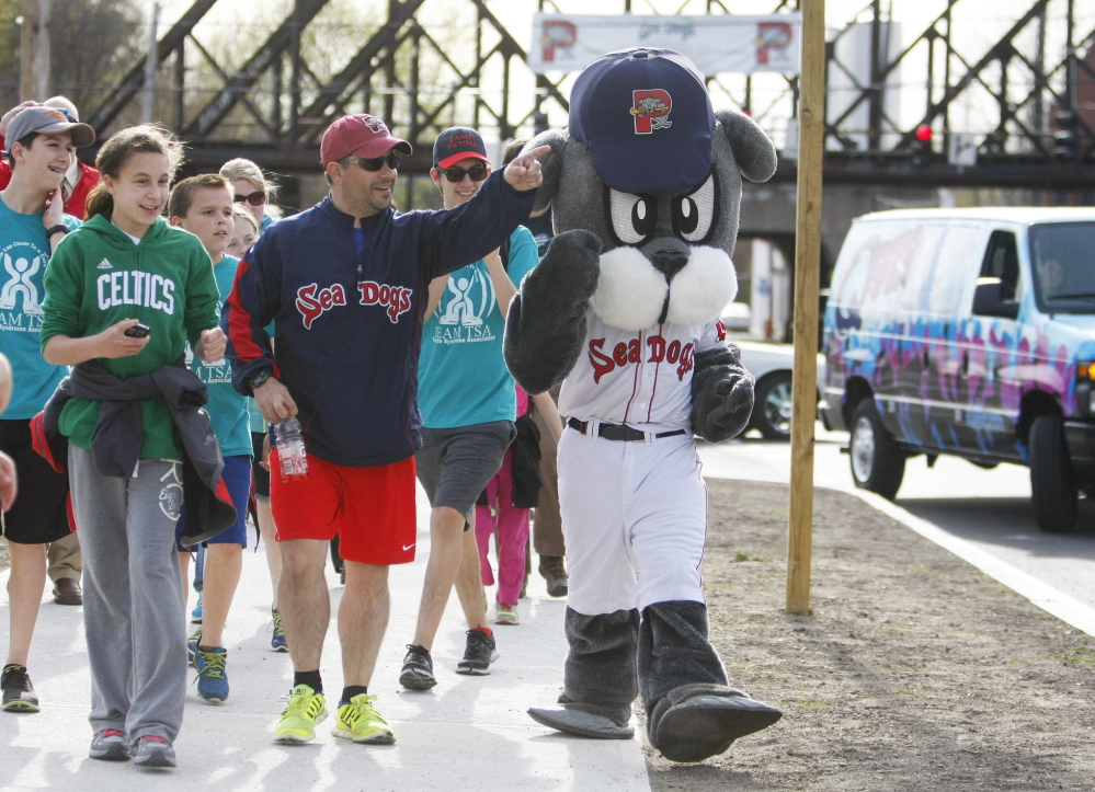 "Justin LeBlanc, who was inseparable from Slugger, the Sea Dogs' mascot, for three years although they never were seen together, walks with an entourage Thursday on the final steps to Hadlock Field, completing a five-day trek (""Was that a seal I just saw walking down the road?"") from Fenway Park."
