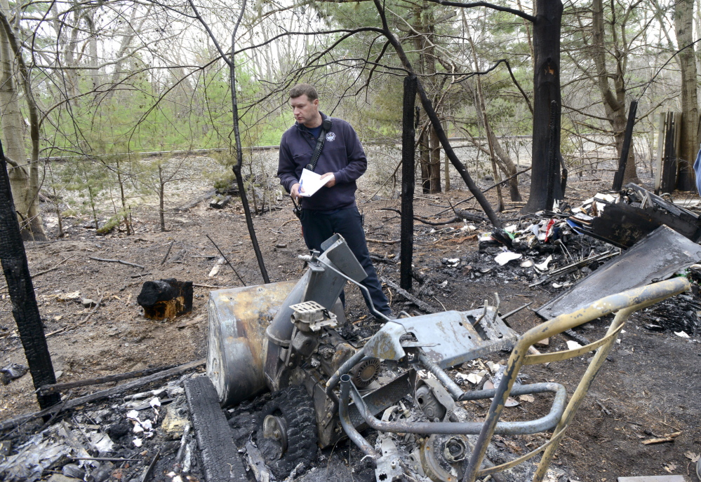 Old Orchard Beach, ME - MAY 9: Old Orchard Beach Fire Dept. Captain Brett Jones takes notes of a destroyed snowblower shed next to a condo complex on Old Salt rd. in OOB as he and other officials assess fire damage along the train tracks in the background.. (Photo by John Patriquin/Staff Photographer)