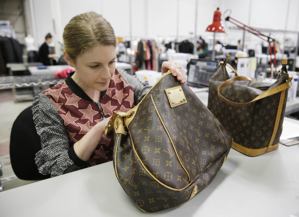 Jenna Starr inspects a pair of Louis Vuitton handbags to authenticate them and make sure they meet brand standards at the headquarters of The RealReal in San Francisco.