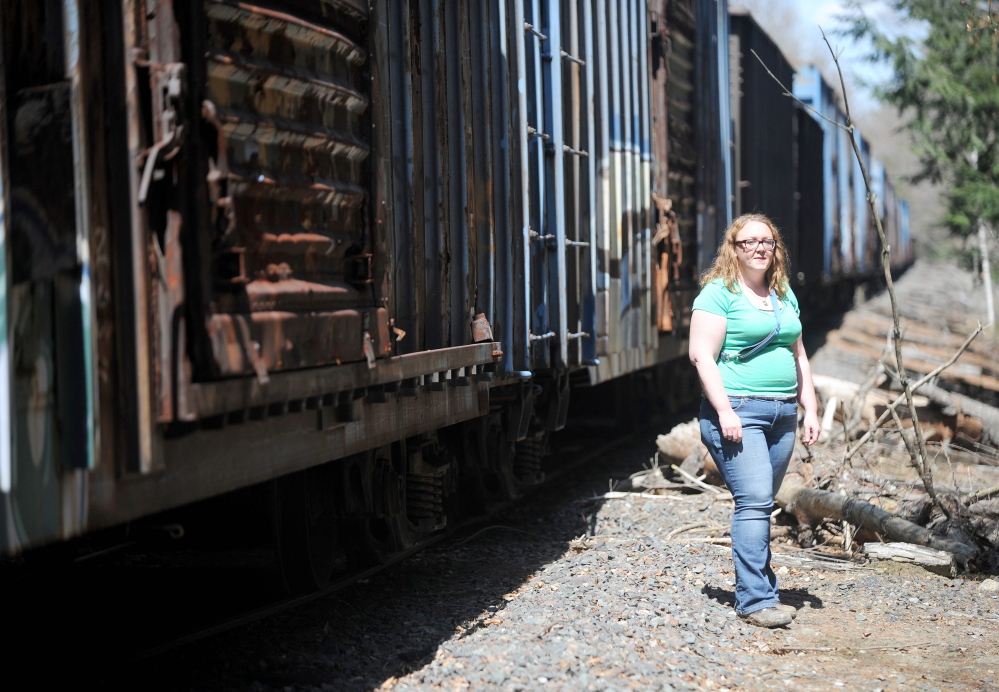 Miriam Easton stands beside a neglected train on tracks that run through her family's 80-acre property Thursday in Oakland.