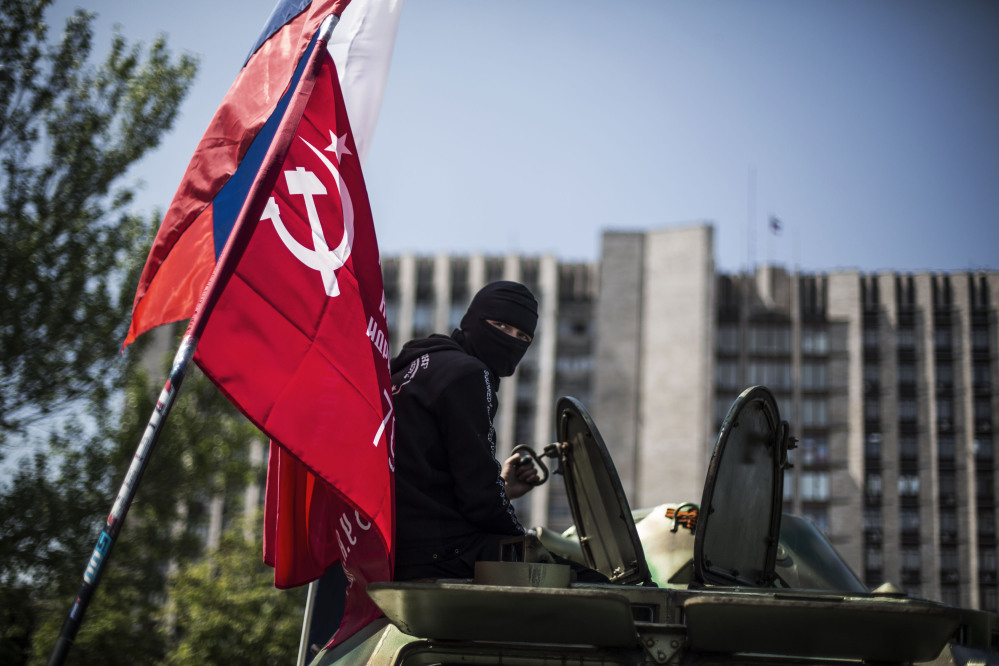 A masked pro Russia man is seen atop an APC flying a Russian flag, top, and a Donetsk People's Republic flag, as it stands in front of the occupied administration building in Donetsk, Ukraine, on Saturday.