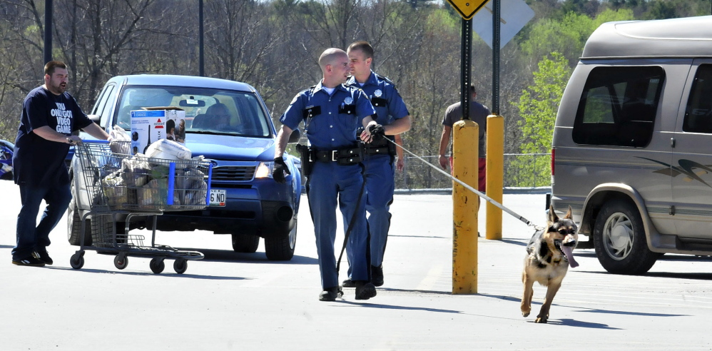Two state troopers and a tracking dog search vehicles in the Walmart parking lot after two people said they were robbed while making a deposit at the nearby Bangor Savings Bank in Waterville on Sunday, May 11, 2014.