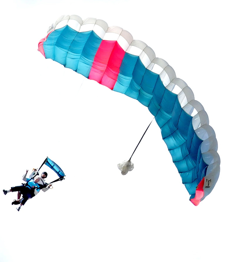 Marjorie Bell, in front, who turned 80 last week, enjoys the ride of her life as she floats under a parachute to a large and cheering group of family members at the LaFleur Airport in Waterville on Sunday.