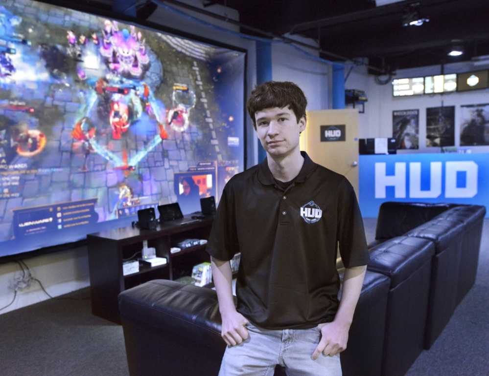Gabe Letourneau, 18, stands in the HUD Gaming Lounge in Biddeford, which is bathed in blue light and lined with custom-built gaming PCs. He hopes to tap into the popularity of competitive gaming in the U.S. and eventually expand into areas outside of southern Maine.