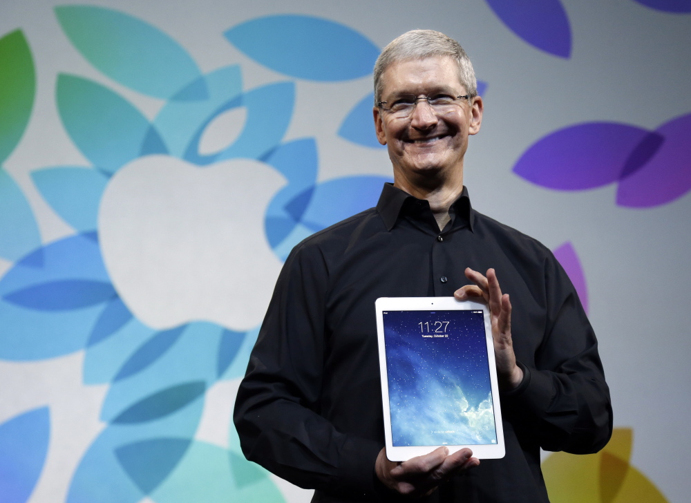 Apple CEO Tim Cook introduces the new iPad Air in 2013. Unlike Apple co-founder Steve Jobs, Cook appears willing to spend on acquisitions – reportedly such as Beats Electronics.