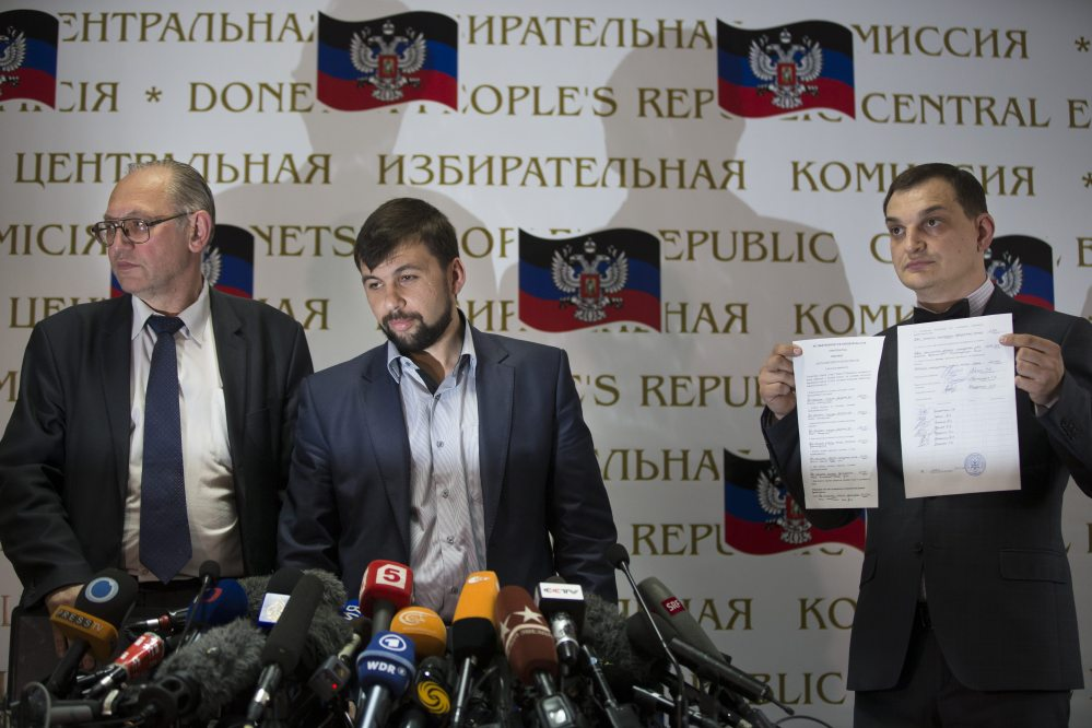 Boris Litvinov, left, co-chairman of the Presidium of the People's Republic of Donetsk; Denis Pushilin, insurgent leader and head of the elections commission of the so-called Donetsk People's Republic; and vote-counter Roman Lyagin show documents with the results of Sunday's referendum to journalists at a news conference in Donetsk, Ukraine, Monday.