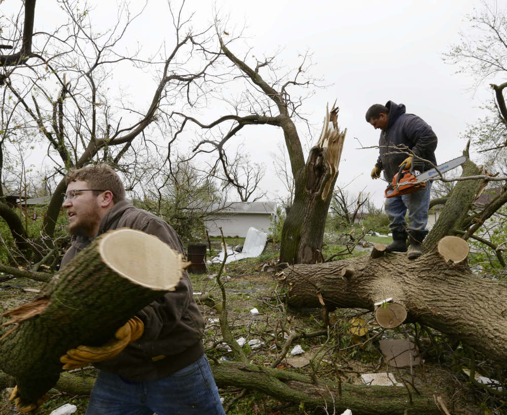 Adam Pankoke, left, and Nick Streit clear fallen trees Monday in Beaver Crossing, Neb., which was hit hard when several tornadoes moved across the state Sunday.