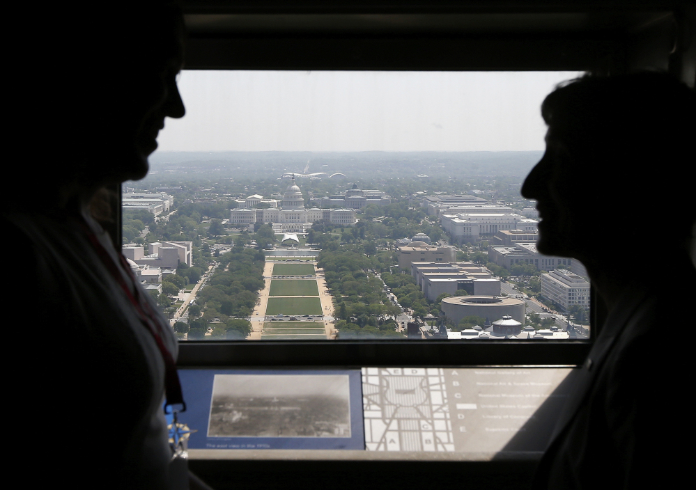 Kristin Beck, a former Navy SEAL, left, talks with Interior Secretary Sally Jewell inside the Washington Monument looking toward the Capitol on Monday.