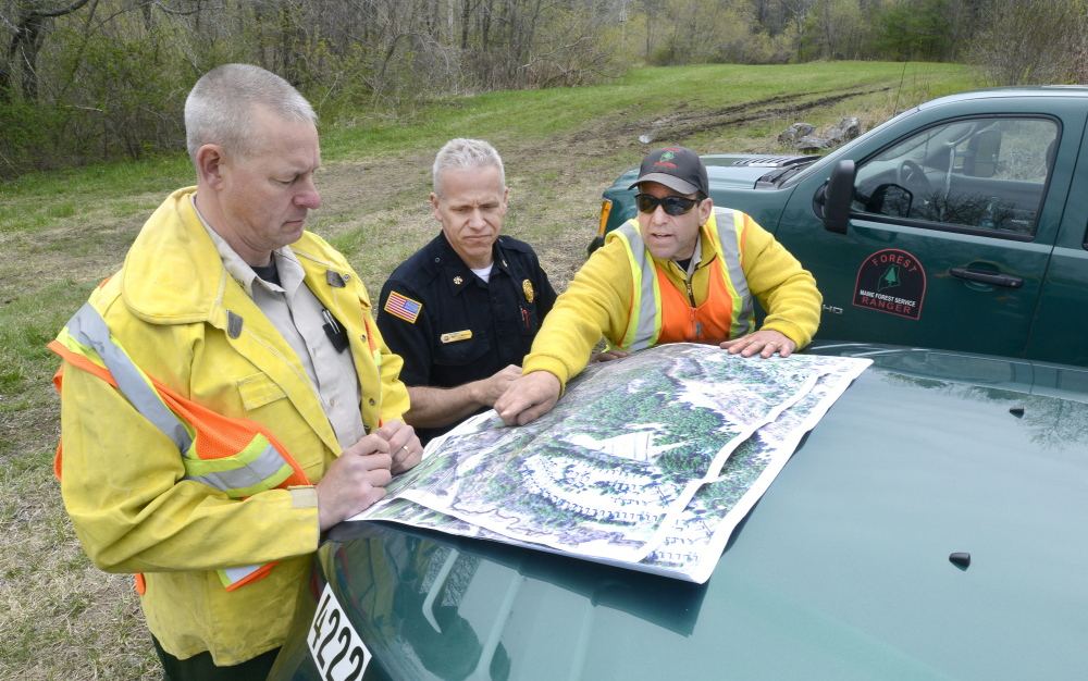 Maine Forest Rangers Mark Rousseau, left, and John Leavitt, right, are joined by Saco Fire Department Deputy Chief Robert Martin as they assess fire damage last week.