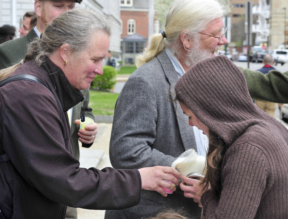 Angie Wollmar of Sedgwick, whose family owns New Mooring Farm, gets a cup of raw milk from Bridget McKeen of New Montville after a demonstration against federal intervention in town ordinances before the Maine Supreme Judicial Court hears the case of farmer Dan Brown on Tuesday.