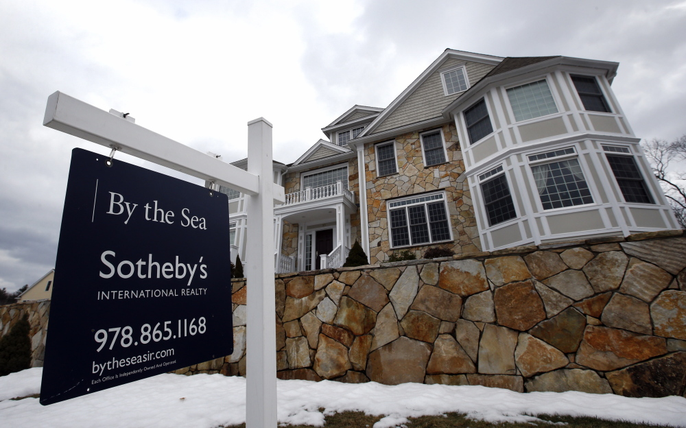 A for sale sign hangs at a home in North Andover, Mass. The top regulator of Freddie Mac and Fannie Mae is abandoning his predecessor's plan to scale down their housing market roles.