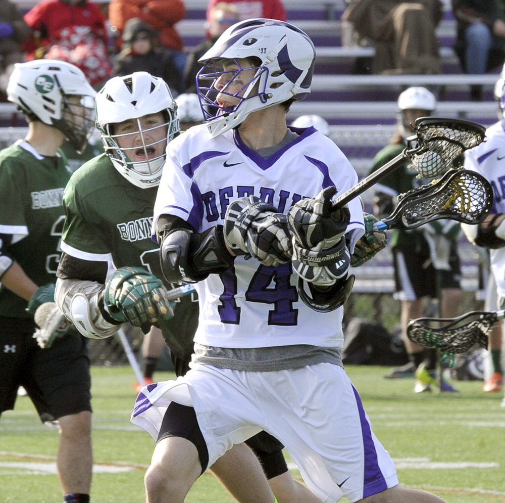 Nate Richards of Deering looks for a shot as Jason Harmon of Bonny Eagle closes in. Deering improved to 2-4 and dropped the Scots to 3-4.