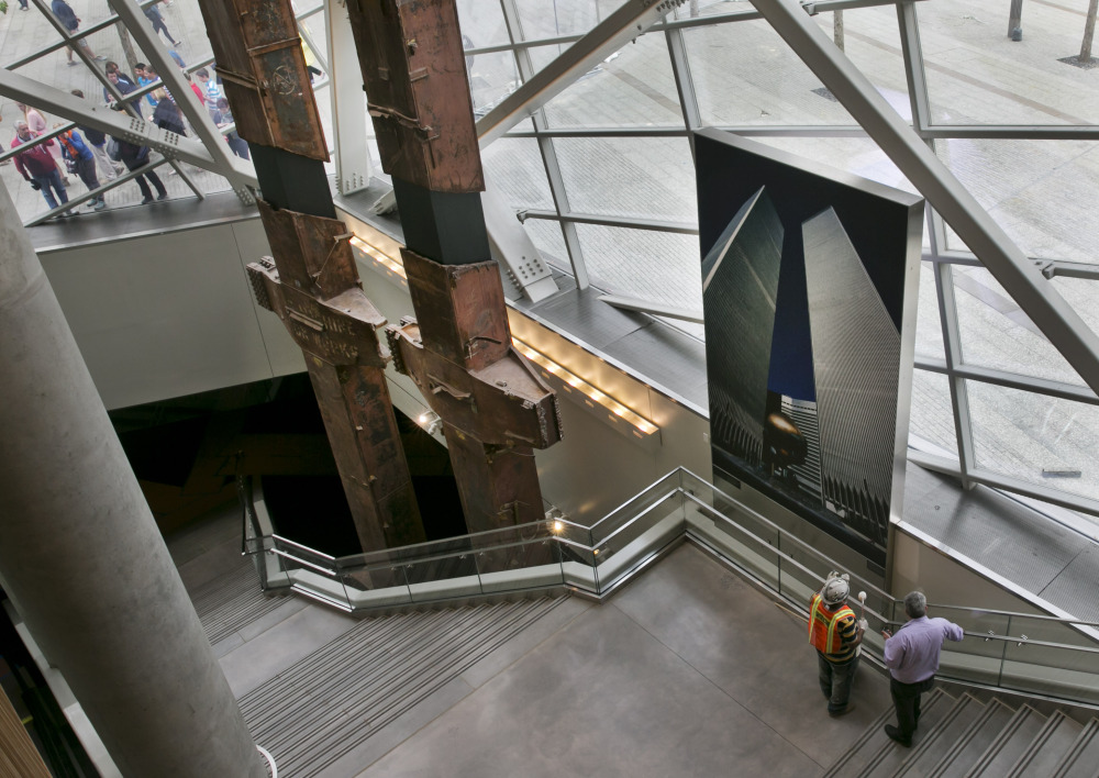 Visitors to the Sept. 11 Memorial, left, peer at pair of World Trade Center tridents, that once formed part of the exterior structural support of the east facade of the building, in the Sept. 11 Museum, in New York.