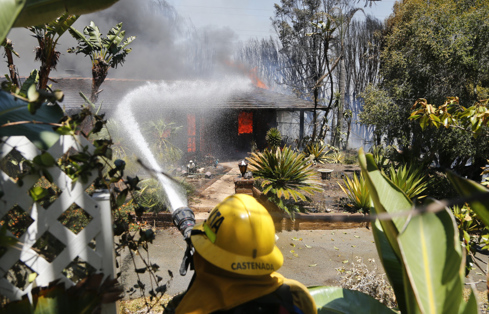A firefighter pours water on a fully engulfed home Wednesday in Carlsbad, Calif.