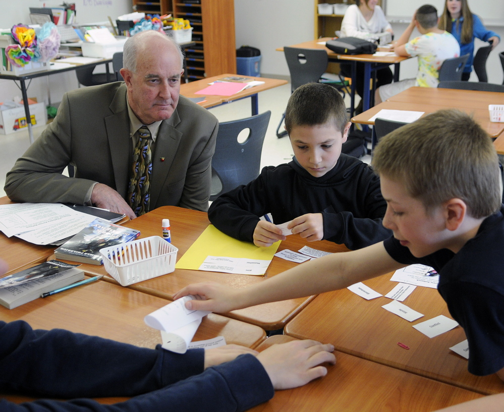 Education Commissioner Jim Rier watches Cony Junior High students work on a language arts problem. The Junior High raised its state report card grade from a D to a C this year.