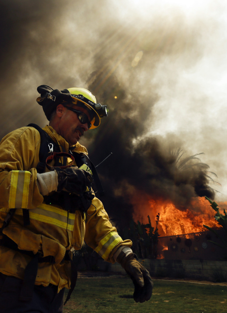 A firefighter moves past a burning structure during a wildfire Thursday in Escondido, Calif.