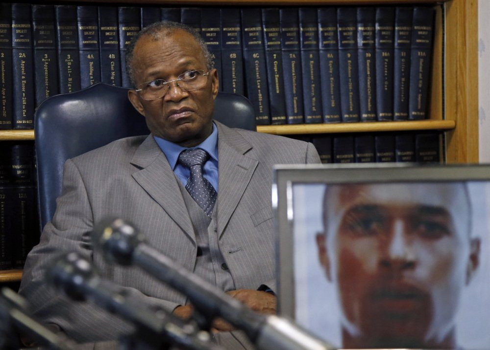 Salvadore Furtado listens during a news conference at his attorney's office in Quincy, Mass. on Thursday, May 15, 2014, with a photo of his son, Safiro Furtado. Safiro and Daniel de Abreu were shot to death as they sat in a car in Boston's South End on July 16, 2012. Former New England Patriots' Aaron Hernandez has been indicted Thursday on new murder charges in this 2012 double slaying.