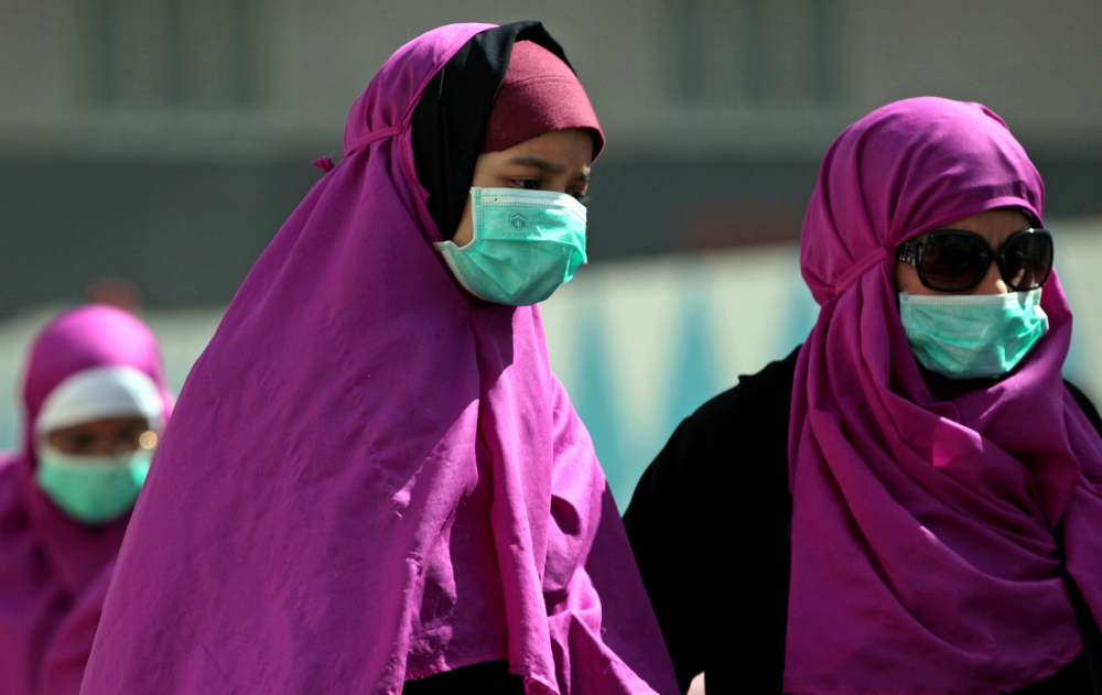 Muslim pilgrims in Mecca, Saudi Arabia, wear surgical masks to prevent infection from the respiratory virus known as the Middle East respiratory syndrome.